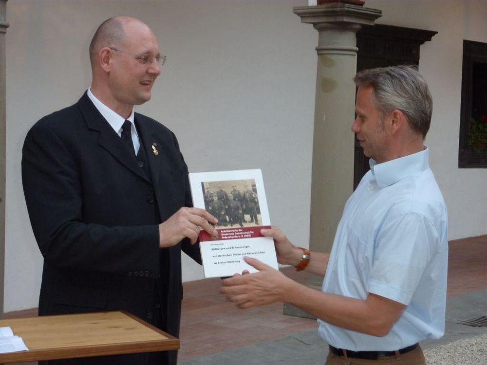 Frank Wörner überreicht nach seinem Grußwort dem Präsidenten der ÖGO, Herrn Dir. Dr. Christian Ortner ein